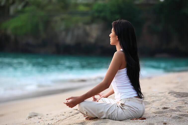 אישה עושה מדיטציה בחוף הים