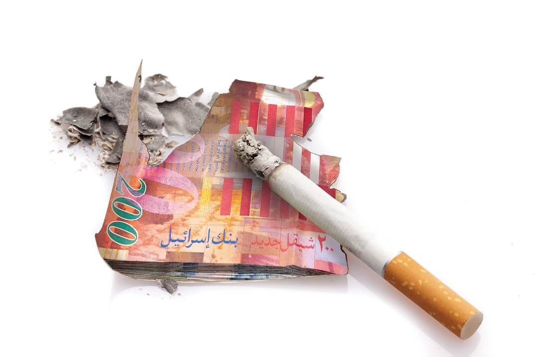 סיגריה על שטרות של כסף נשרפת